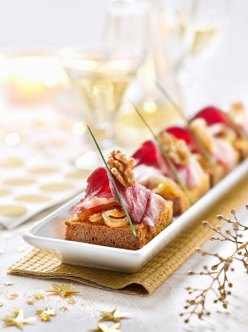 Canapés: honey cake with onion compote, smoked duck breast and walnuts