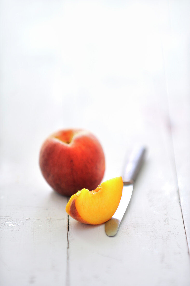 Whole and a quarter of a yellow peach
