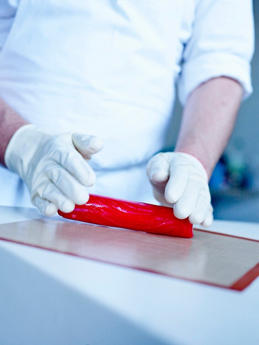 Shaping the raspberry sugar paste into a sausage
