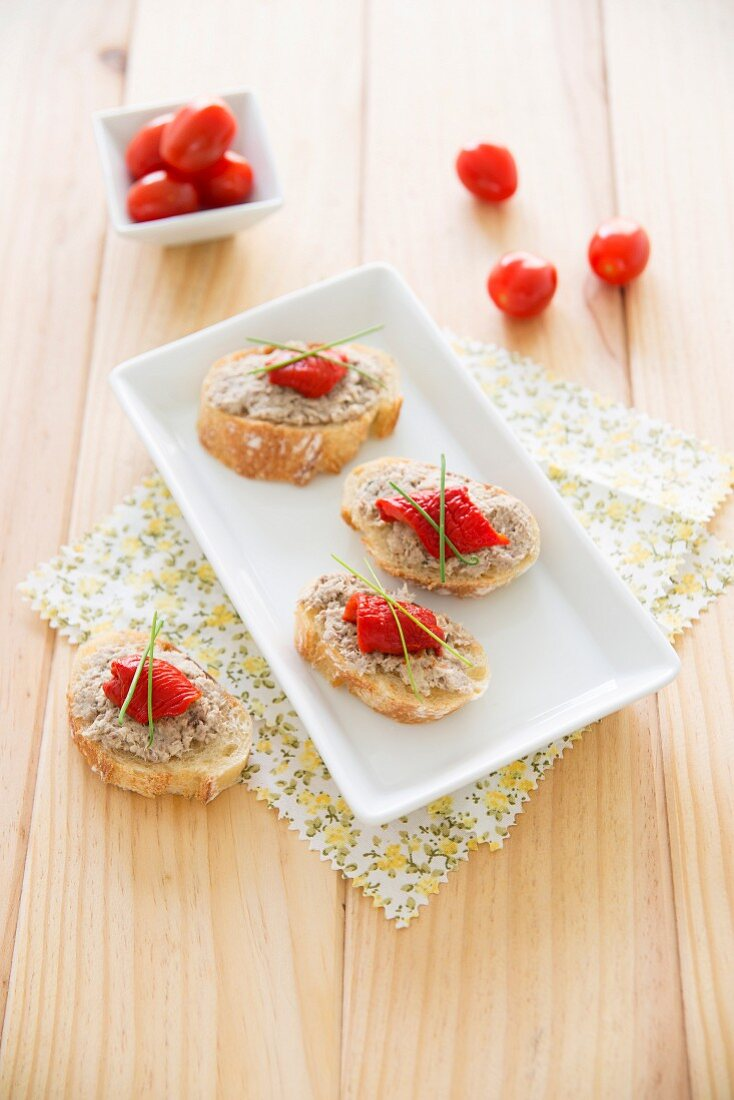 Tuna paté on sliced baguette garnished with lemon, chives and grilled red pepper