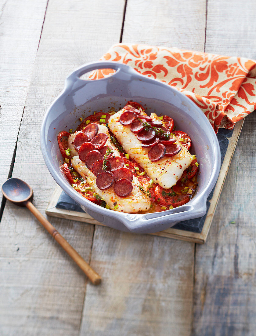 Cod fillets coated in thinly sliced chorizo and tomatoes with thyme before cooking