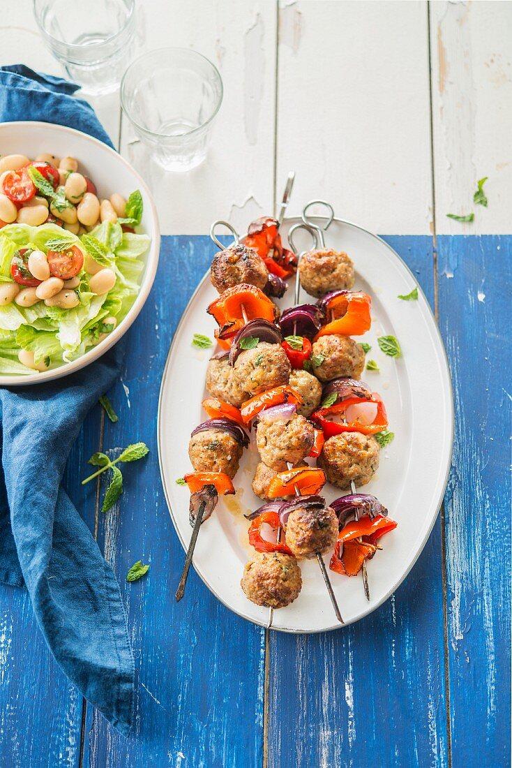 Spiesse mit Fleischbällchen, Zwiebel und Paprika, dazu Salat mit weissen Bohnen und Tomaten