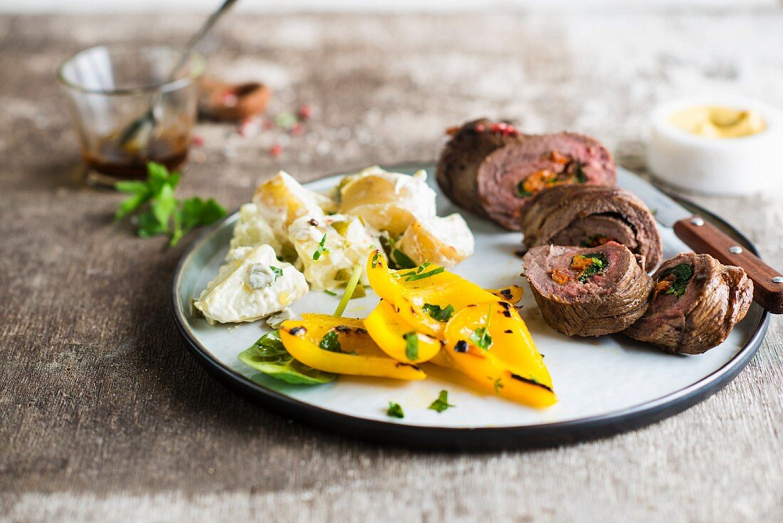 Rolled beef fillet stuffed with spinach and confit tomatoes, potato salad and grilled yellow peppers