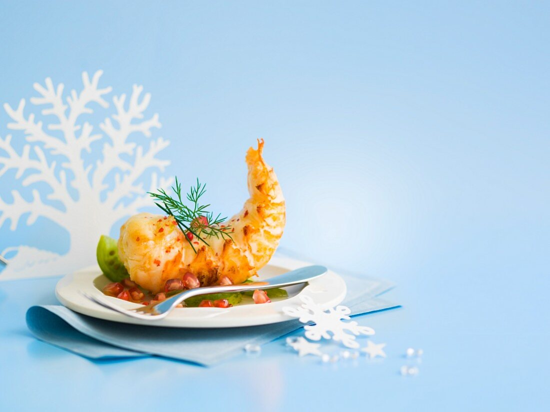 Raw spiny lobster tail with pink pepper, pomegranate seeds and green tomatoes