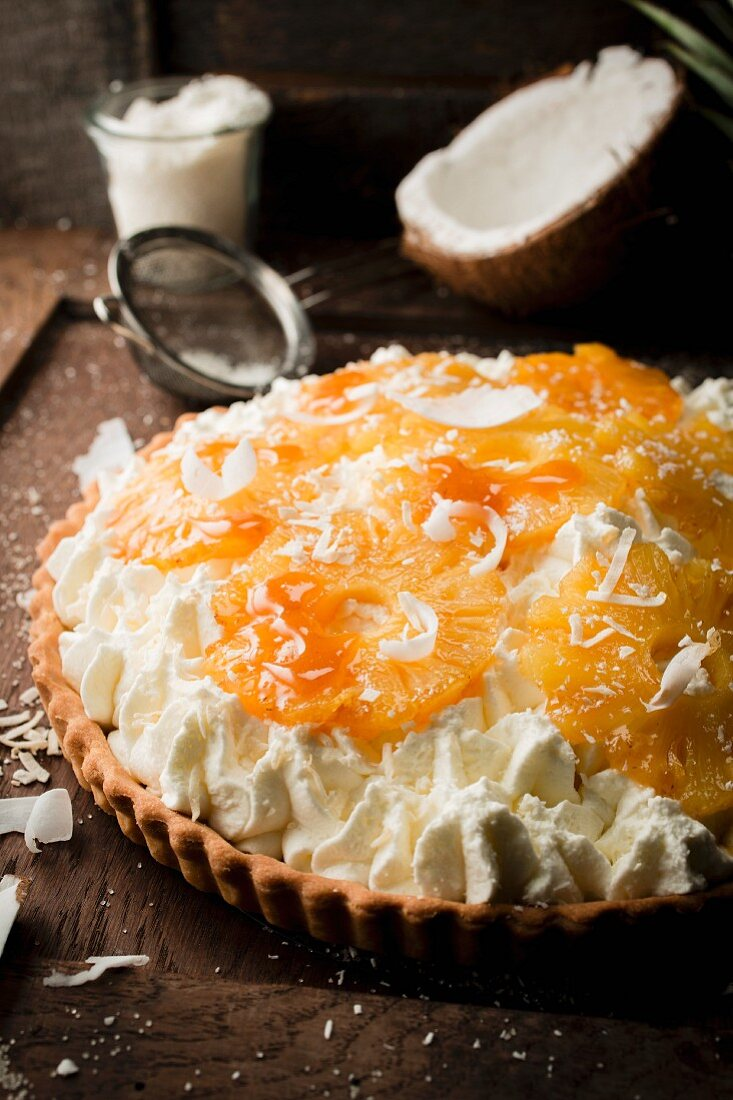 Topping the whipped cream with the roasted pineapple rings and grated coconut