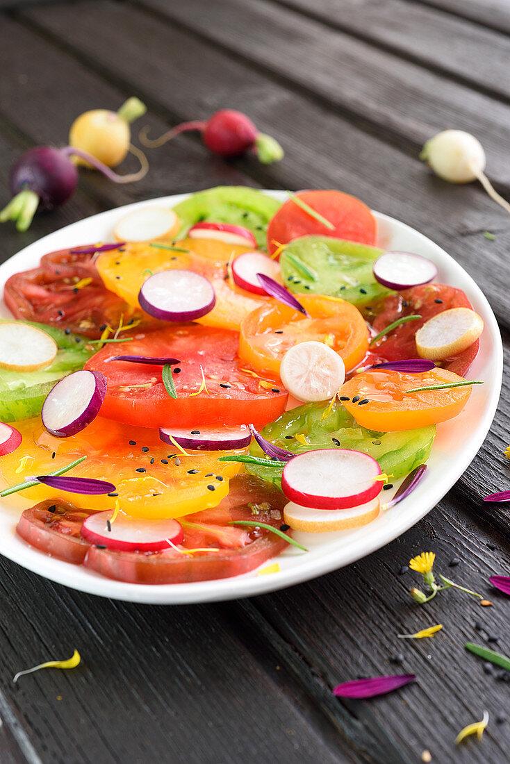 Tomato, radish, sesame seed and dandelion petal multicolored salad