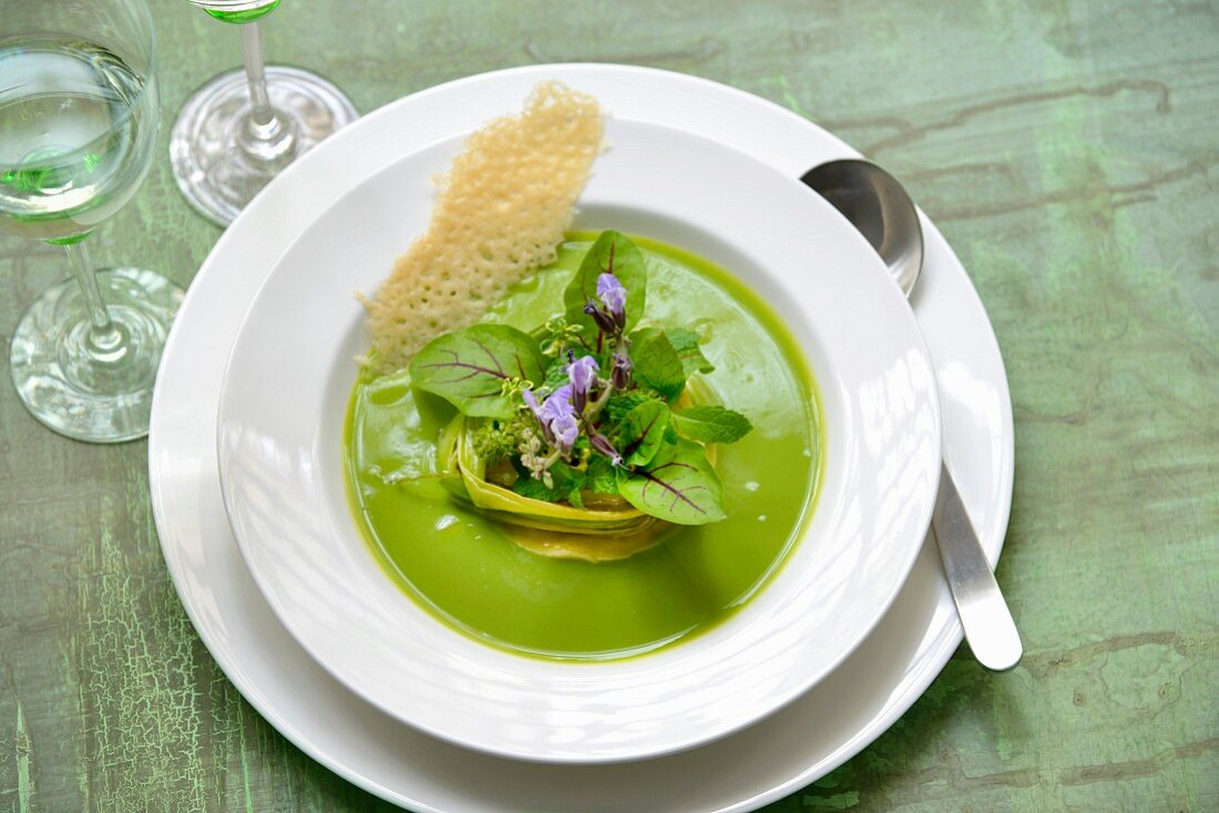 Cream of pea soup with leeks, beetroot leaves, mint and edible flowers, parmesan tuile