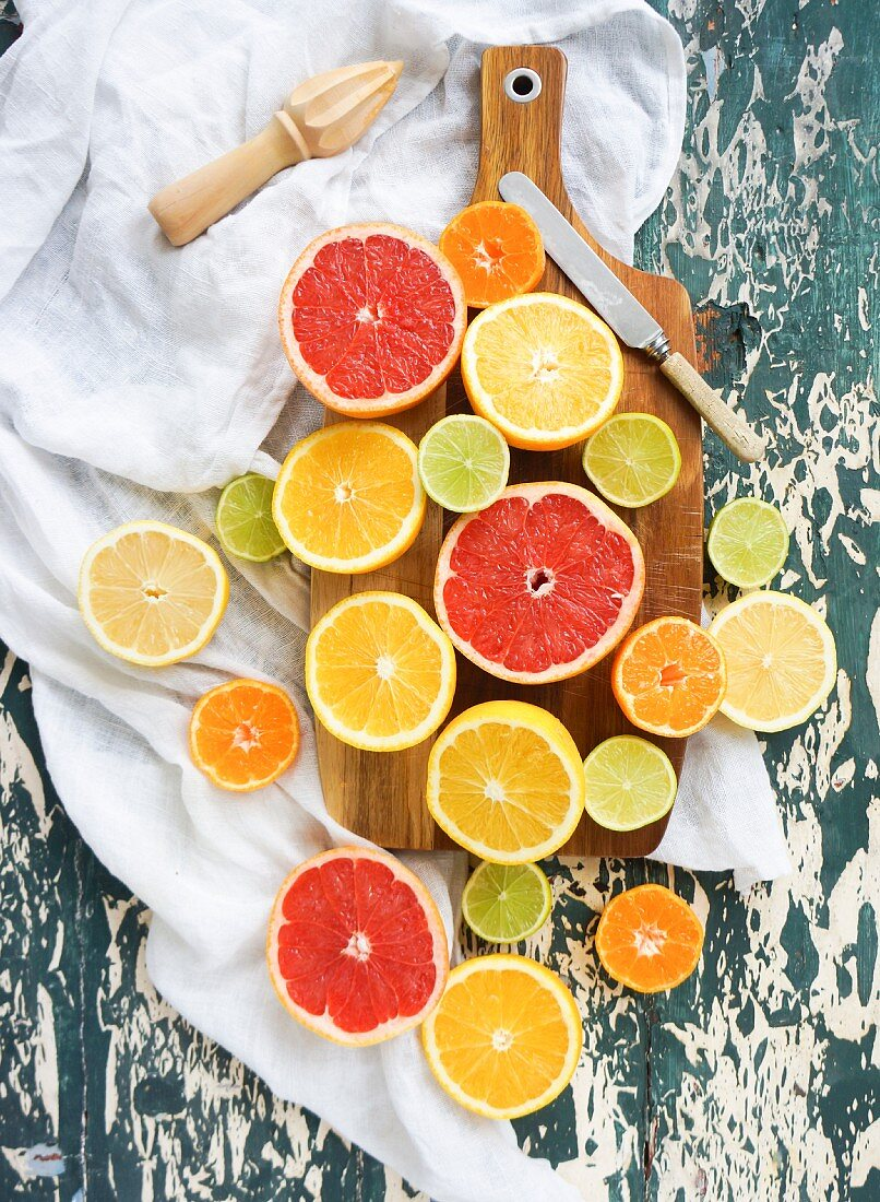 Mixed citrus fruit halves on a chopping board