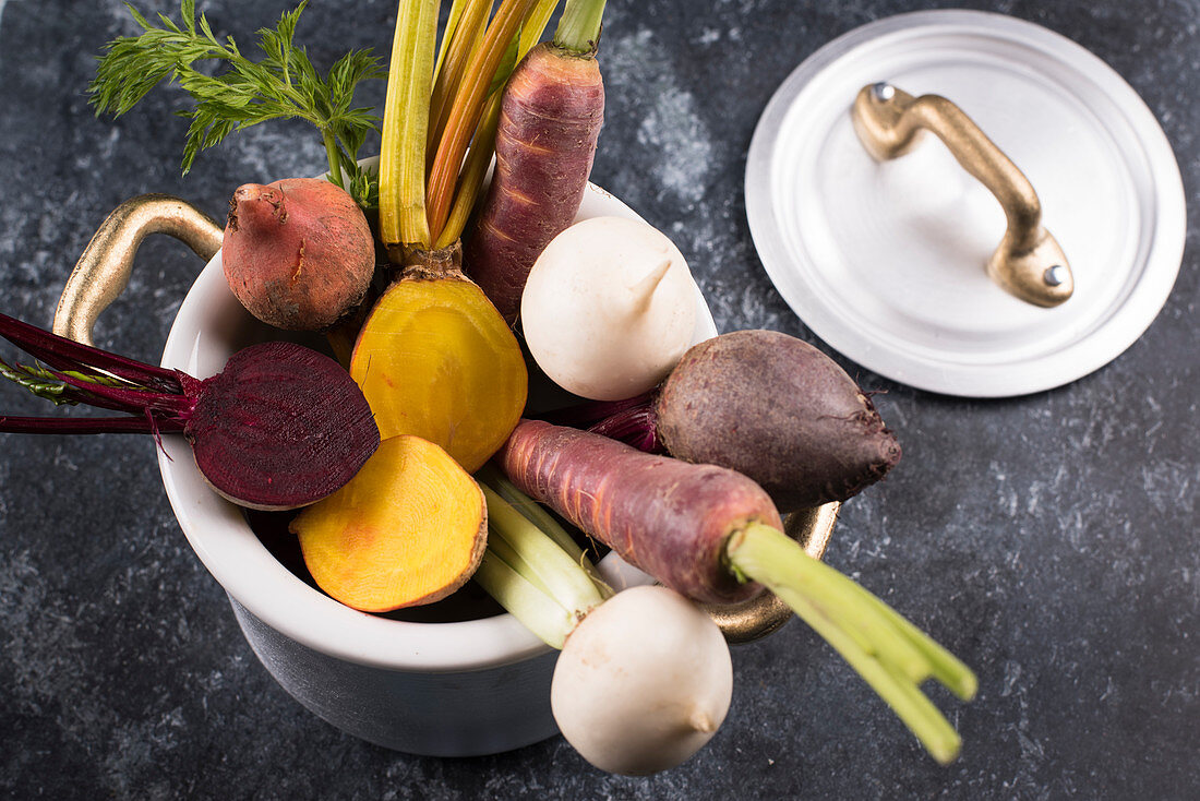 Autumn-winter vegetables in a cooking pot on a black background