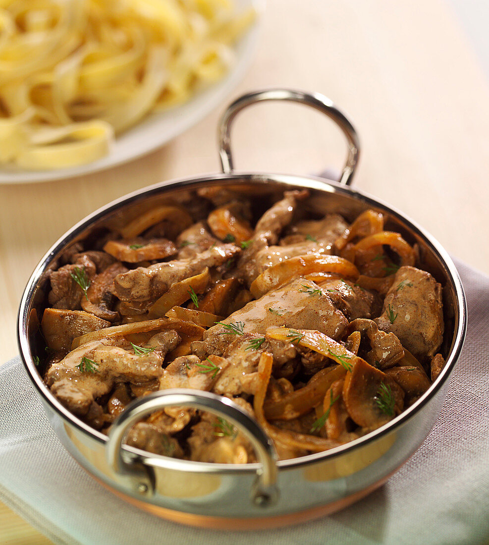 Thinly sliced beef with onions and button mushrooms