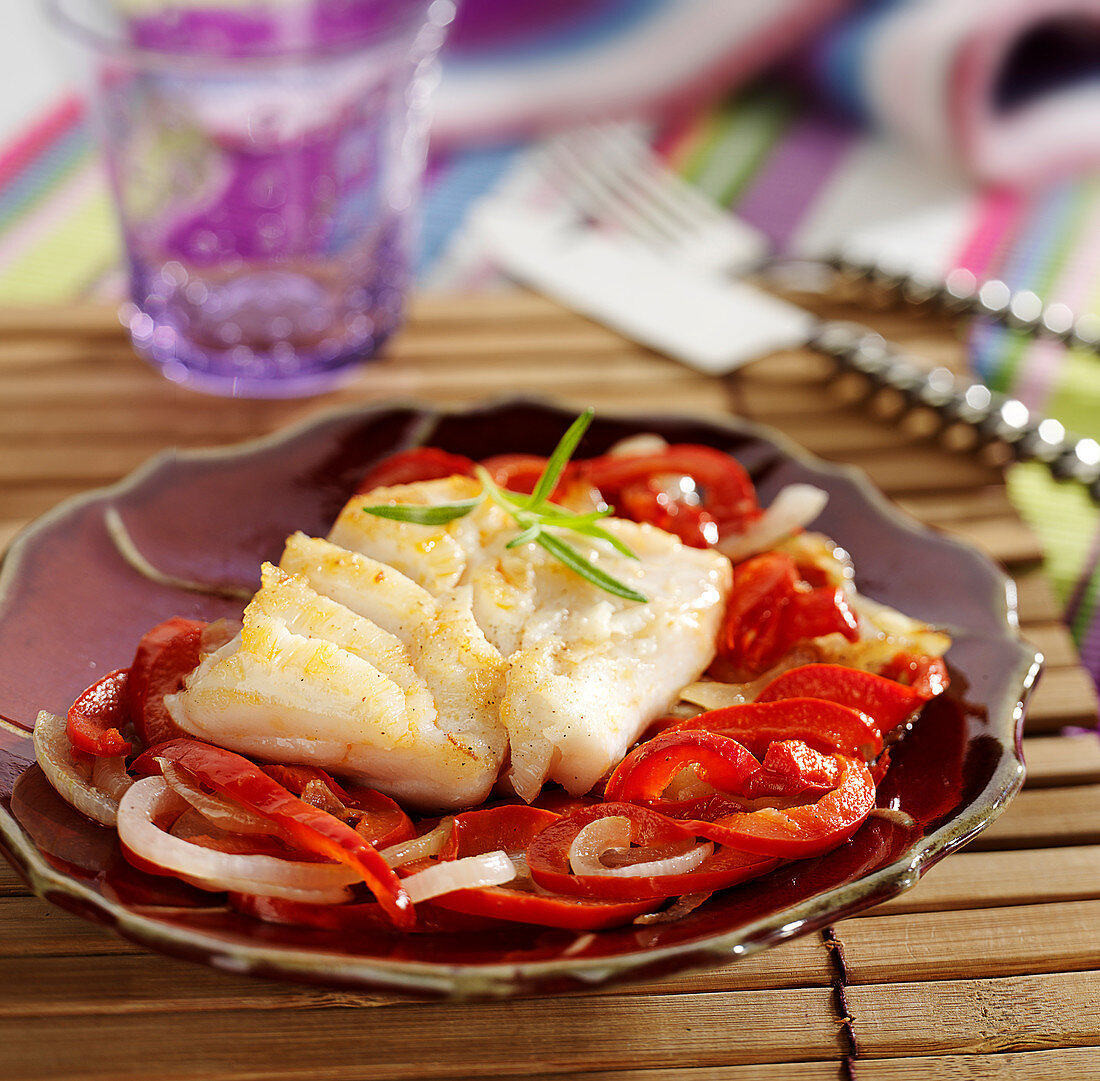 Piece of cod with onions and peppers with paprika