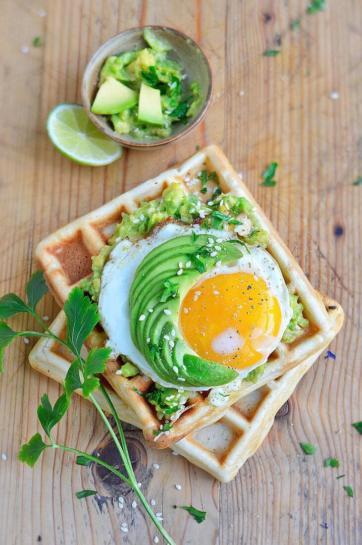 Potato waffles with guacamole, fried egg and sliced avocado