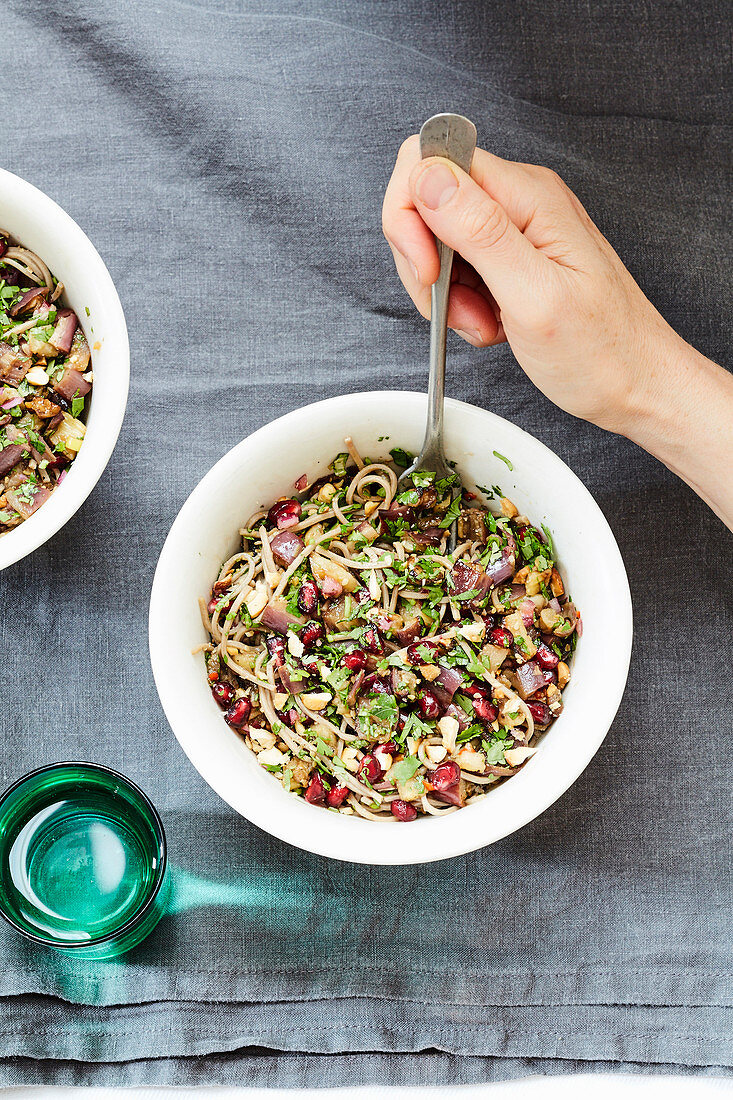 Noodles with aubergines,pomegranate seeds and fresh herbs
