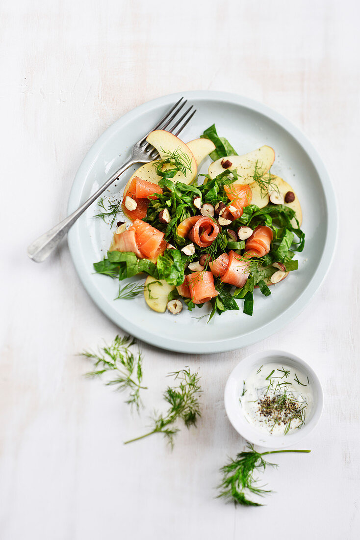 Spinach salad with smoked trout rolls,apple,hazelnuts and dill