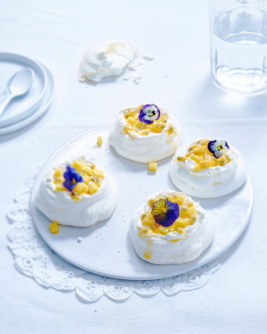 Mini pavlovas with mango, passion fruit and edible pansy flowers