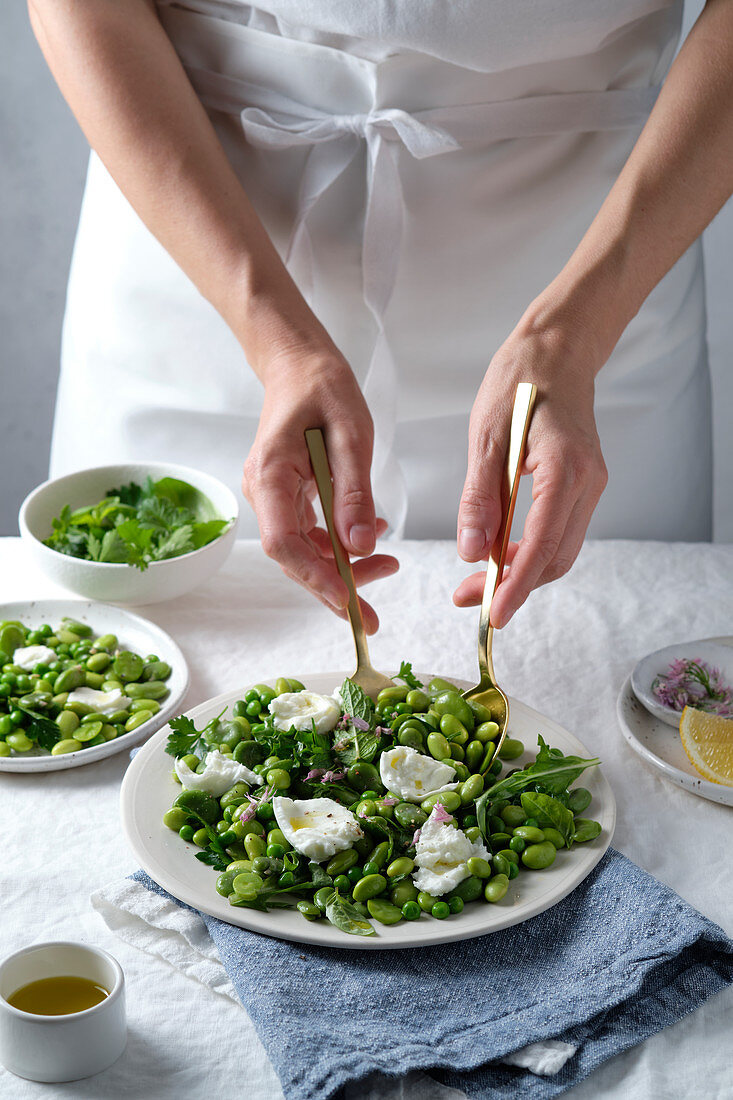 A salad of broad beans (fava beans), edamame, green peas, with burrata cheese and herbs, and olive oil and lemon vinaigrette