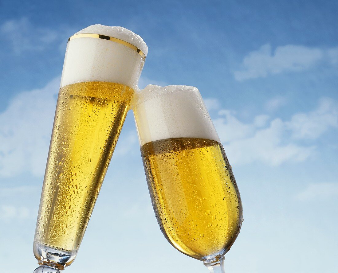 Two Clinking Beer Glasses Against a Blue Sky