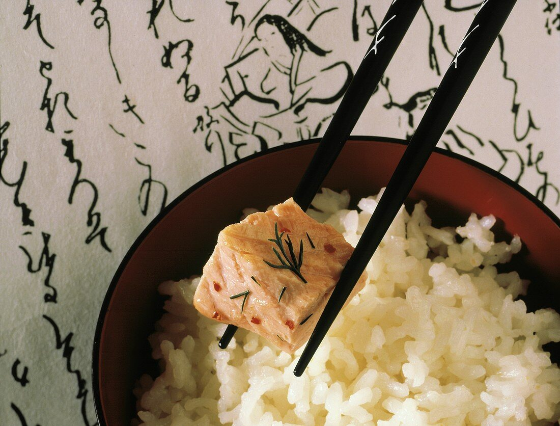 Piece of Salmon in Chopstick; White Rice