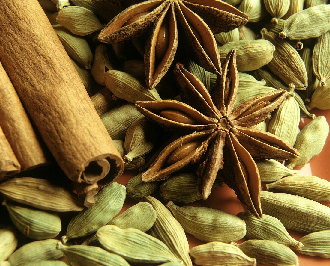 Cinnamon Sticks and Star Anise on Field of Cardamom Seeds