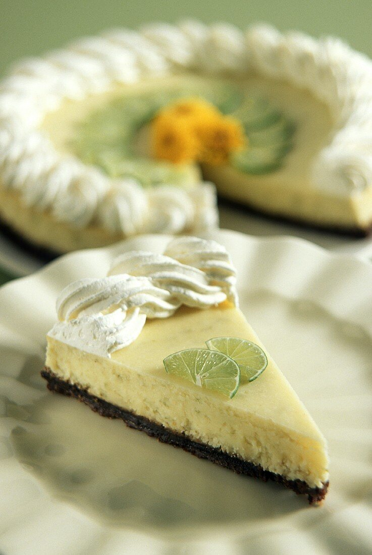 Piece of Key Lime cheesecake on plate, whole cake behind