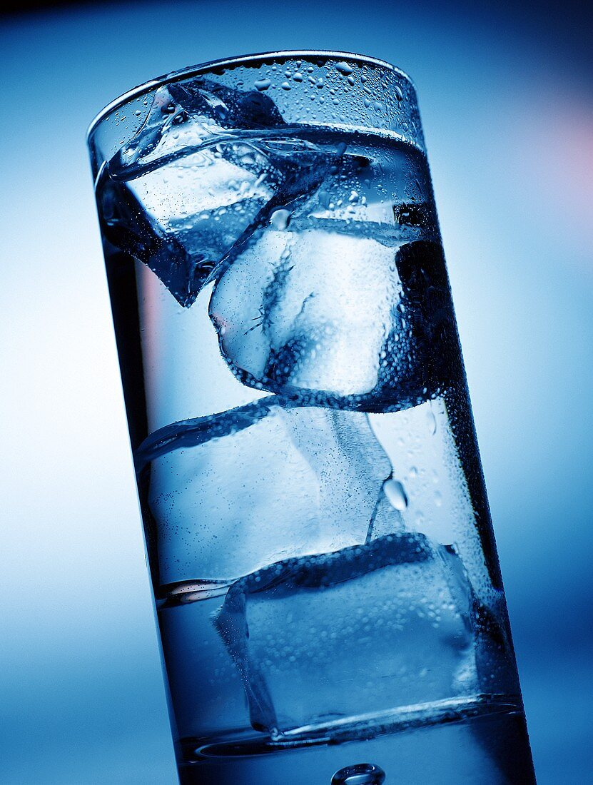 Glass of water with ice cubes in blue light