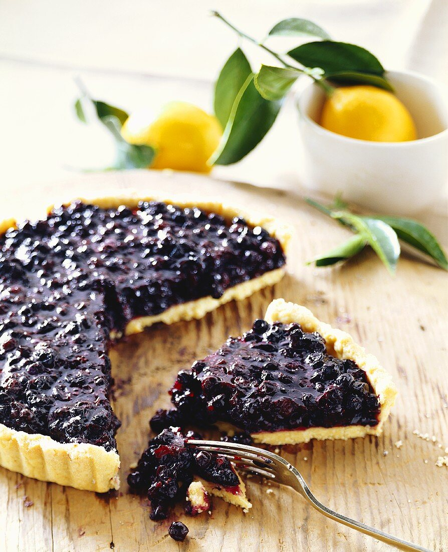 Piece of blueberry tart in front of tart with piece cut