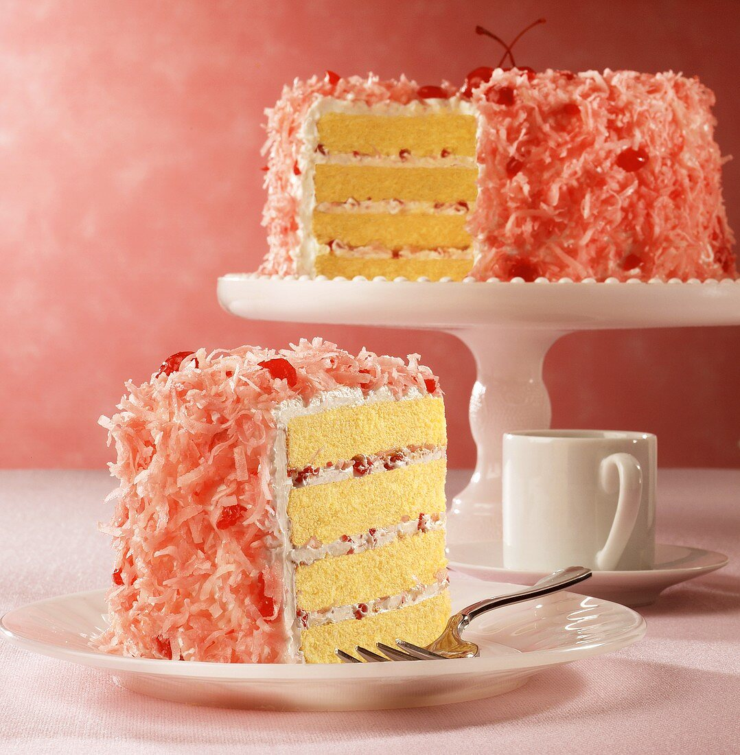 Cherry and coconut cake, slices cut, one slice on plate