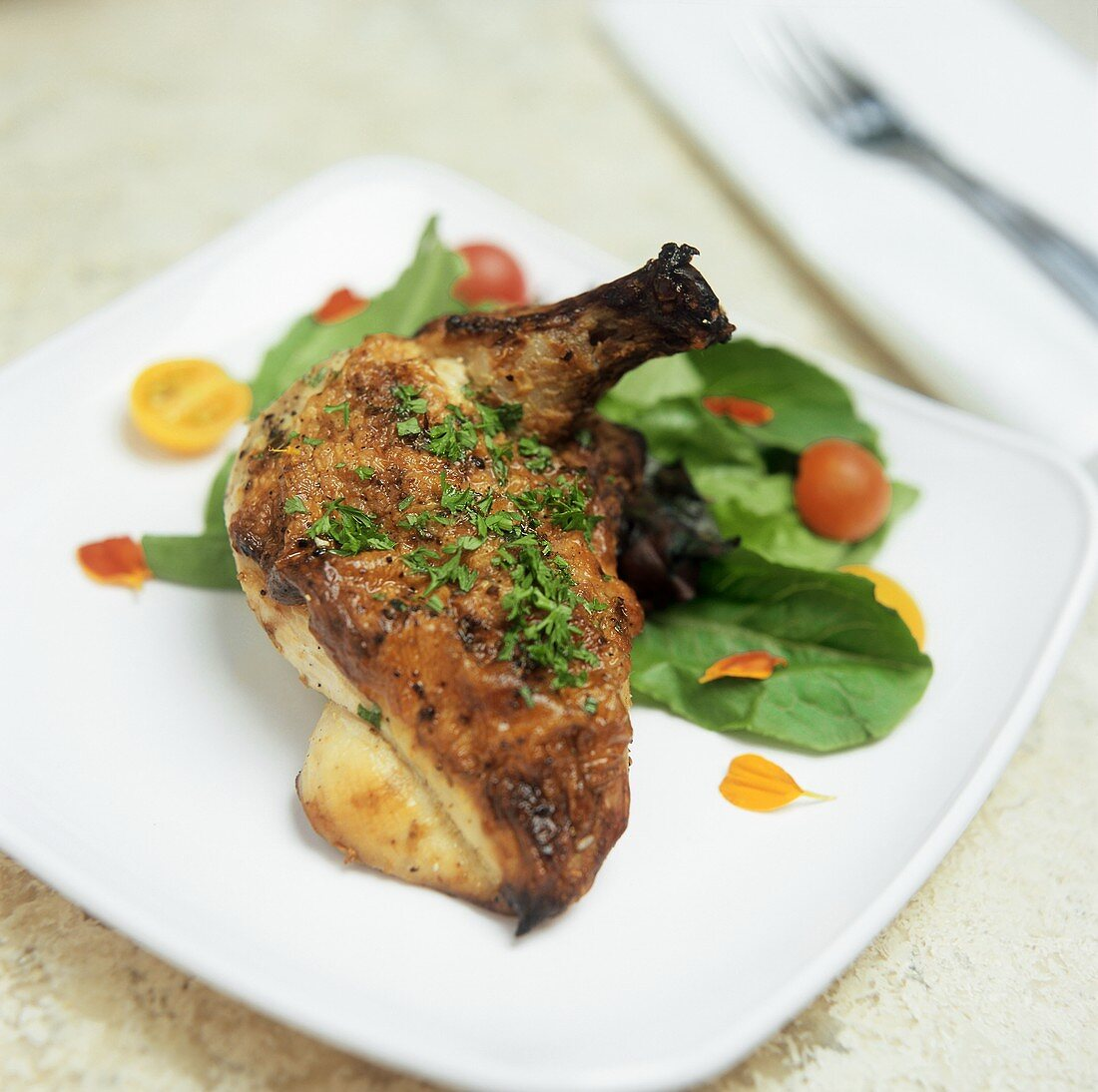 Glazed chicken leg with salad garnish