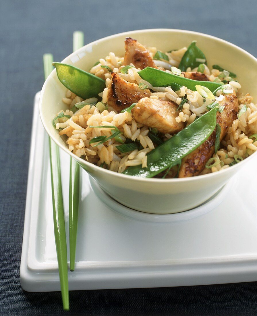 Brown Rice with Chicken, Snow Peas and Scallions on a Tray with Chopsticks