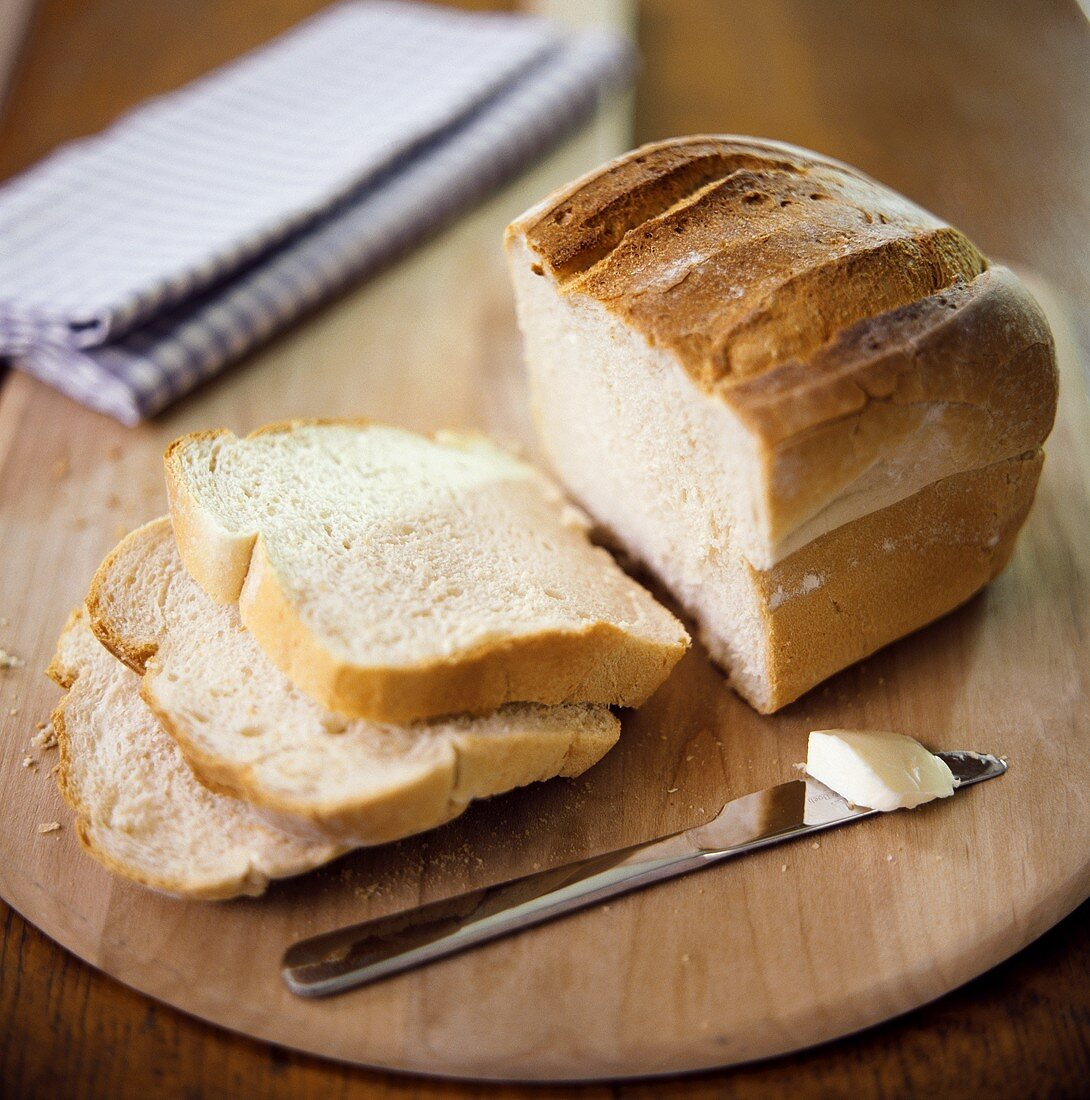 A Partially Sliced Loaf of White Bread on a Wooden Board