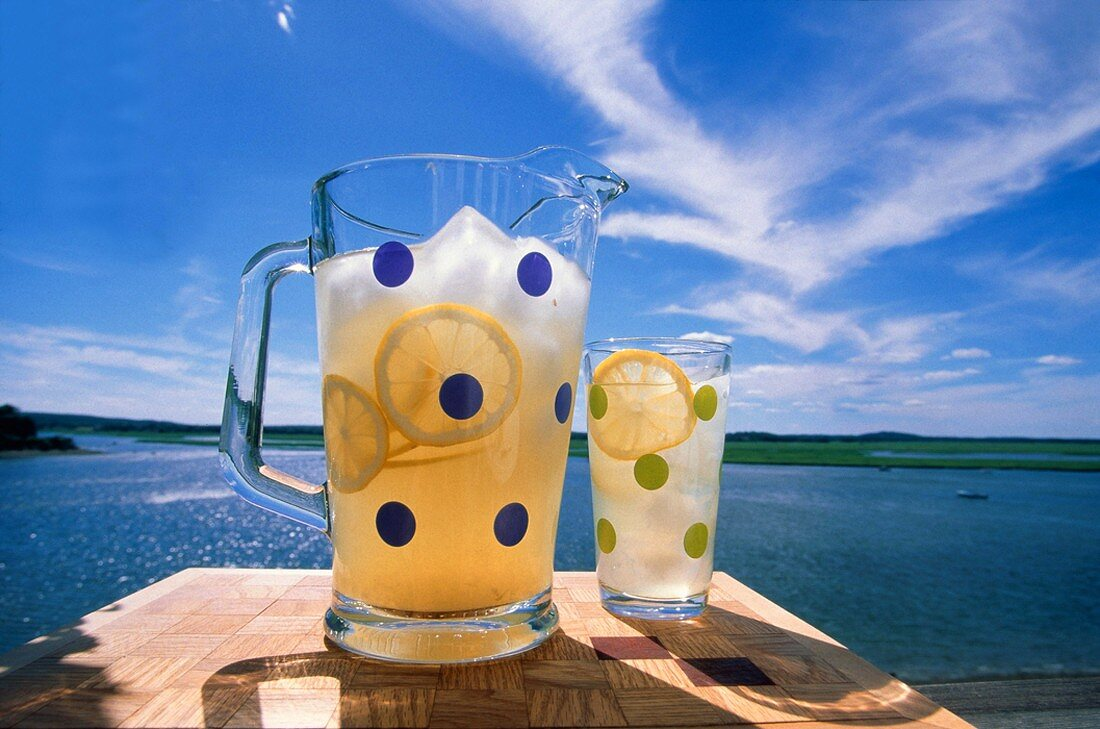 A Pitcher and Glass of Lemonade on a table Overlooking a Lake
