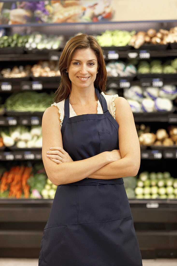 Female employee in supermarket vegetable section