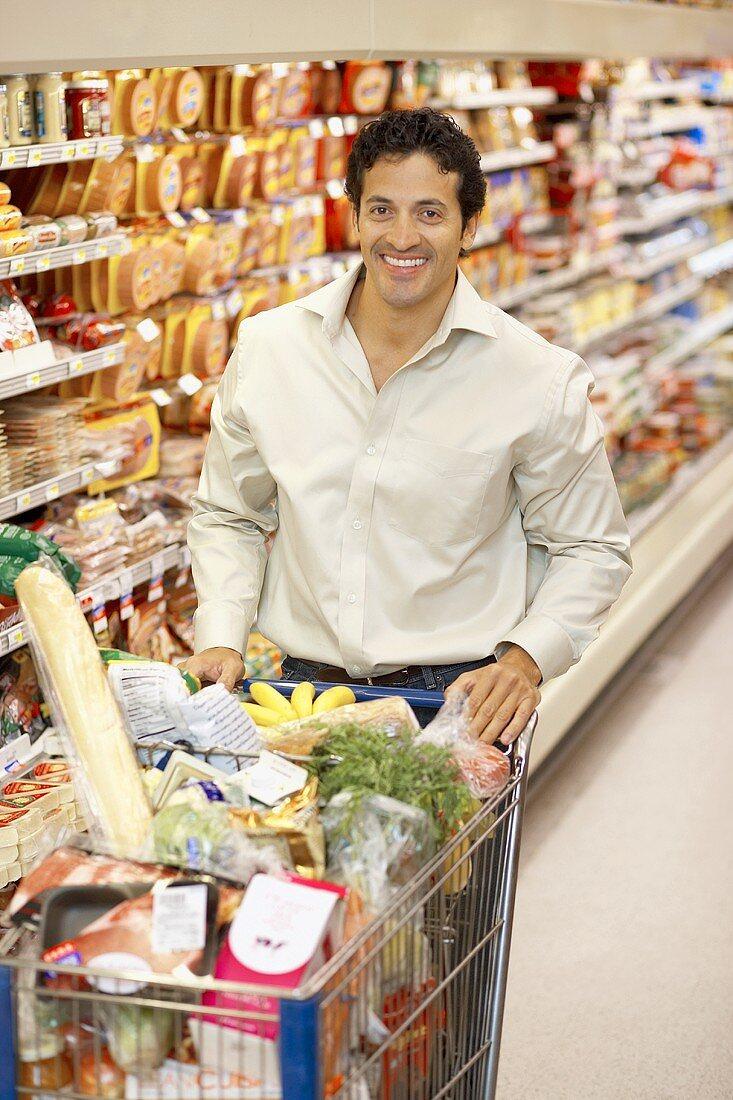 Smiling man pushing full shopping trolley in a supermarket
