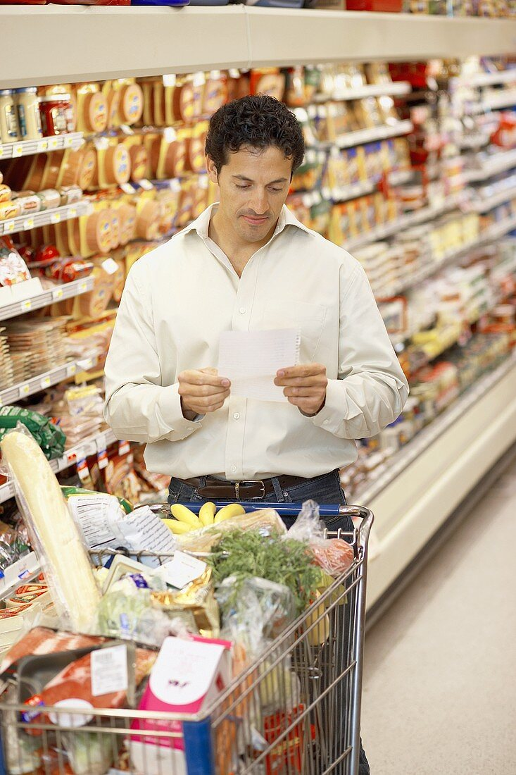 Man reading shopping list in a supermarket