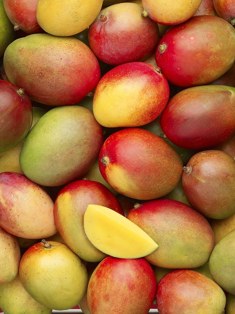 Many whole mangos and a wedge of mango (full-frame)