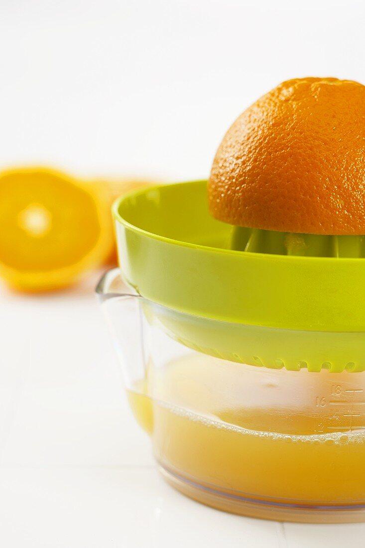 Orange Half on a Juicer with Freshly Squeezed Orange Juice