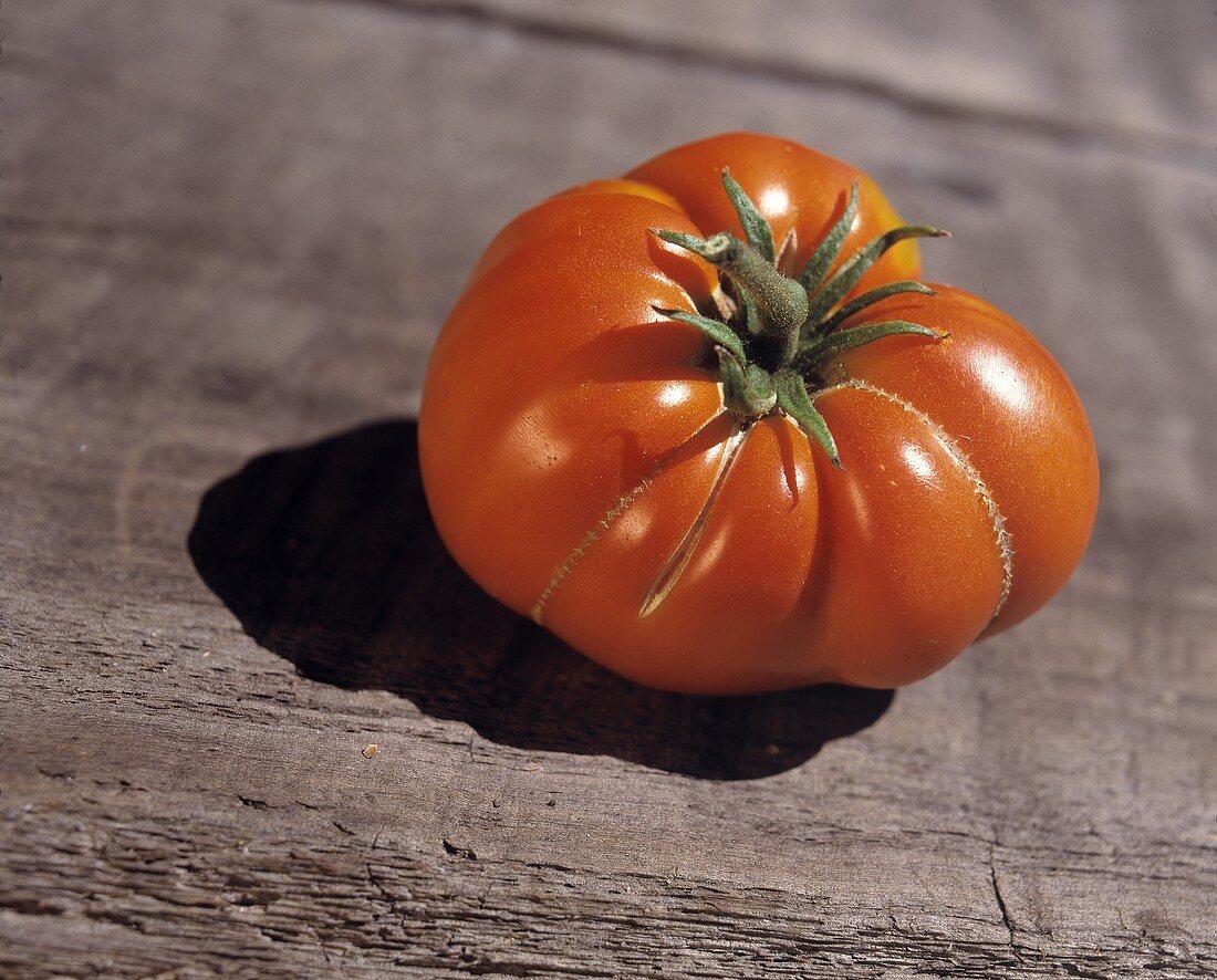One Beefsteak Tomato on Wood