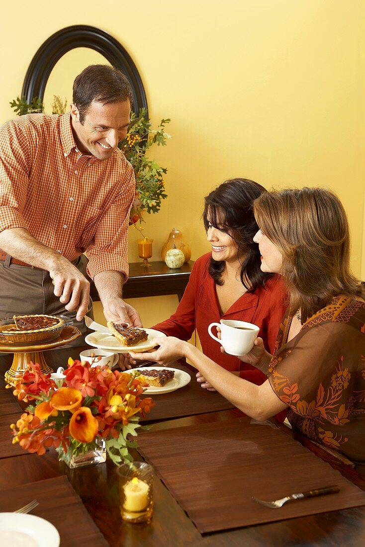 Man Placing a Piece of Pie on Woman's Plate as She Sits at the Thanksgiving Table Holding Cup of Coffee