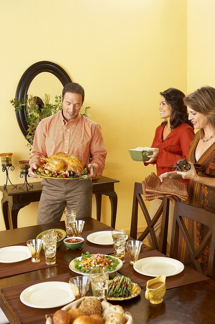 Man and Women Setting Table For Thanksgiving, Man Holding Platter with Roast Turkey