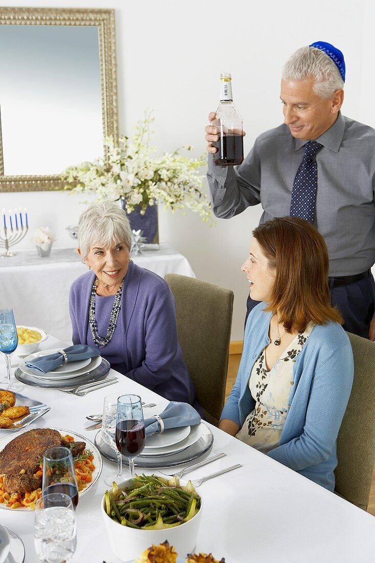 Two Woman Sitting at Hanukkah Table, Man with Bottle of Red Wine