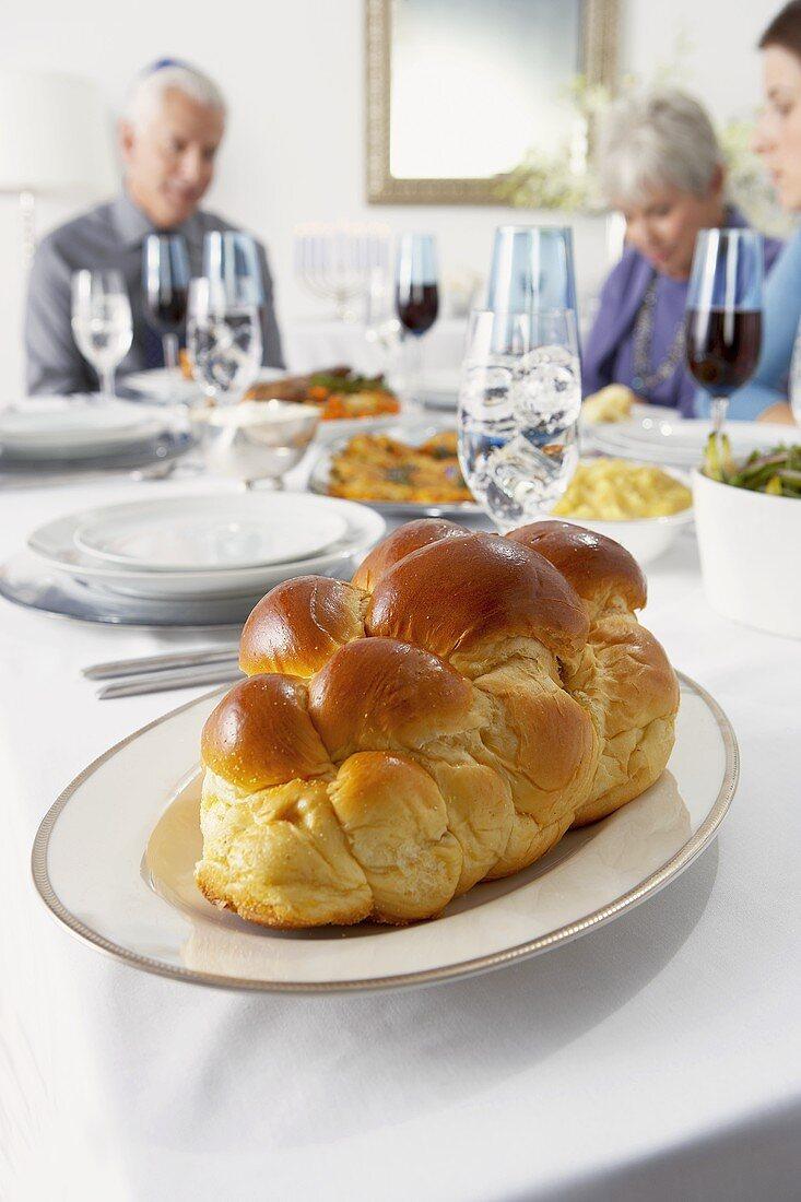 Challah Bread on Hanukkah Table, People Sitting at Table
