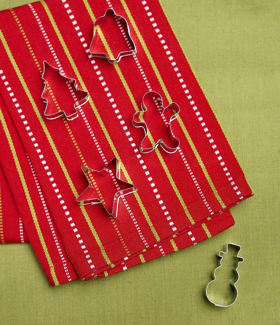 Four Christmas Cookie Cutters on Red and Green Dish Cloth