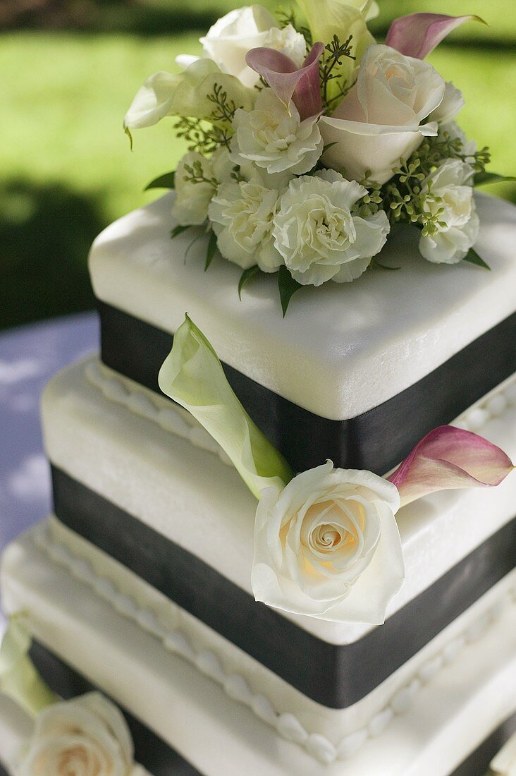 Three Tiered Wedding Cake Decorated with Roses and Calla Lilies