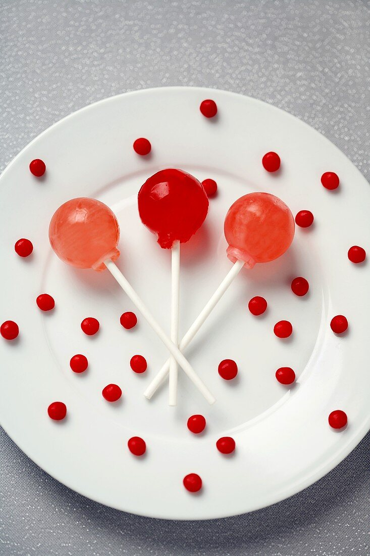 Three Lollipops with Small Red Candies on a White Plate
