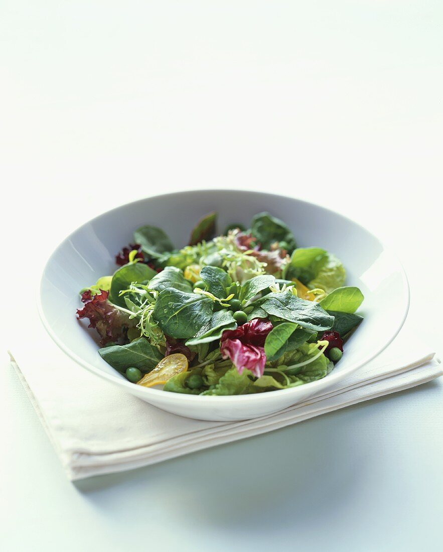 Mixed Green Salad with Peas in a White Bowl