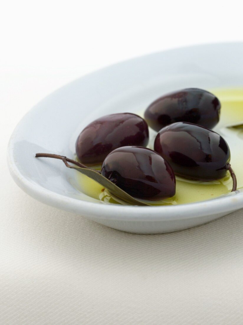 Four Kalamata Olives in a Small Dish with Oil