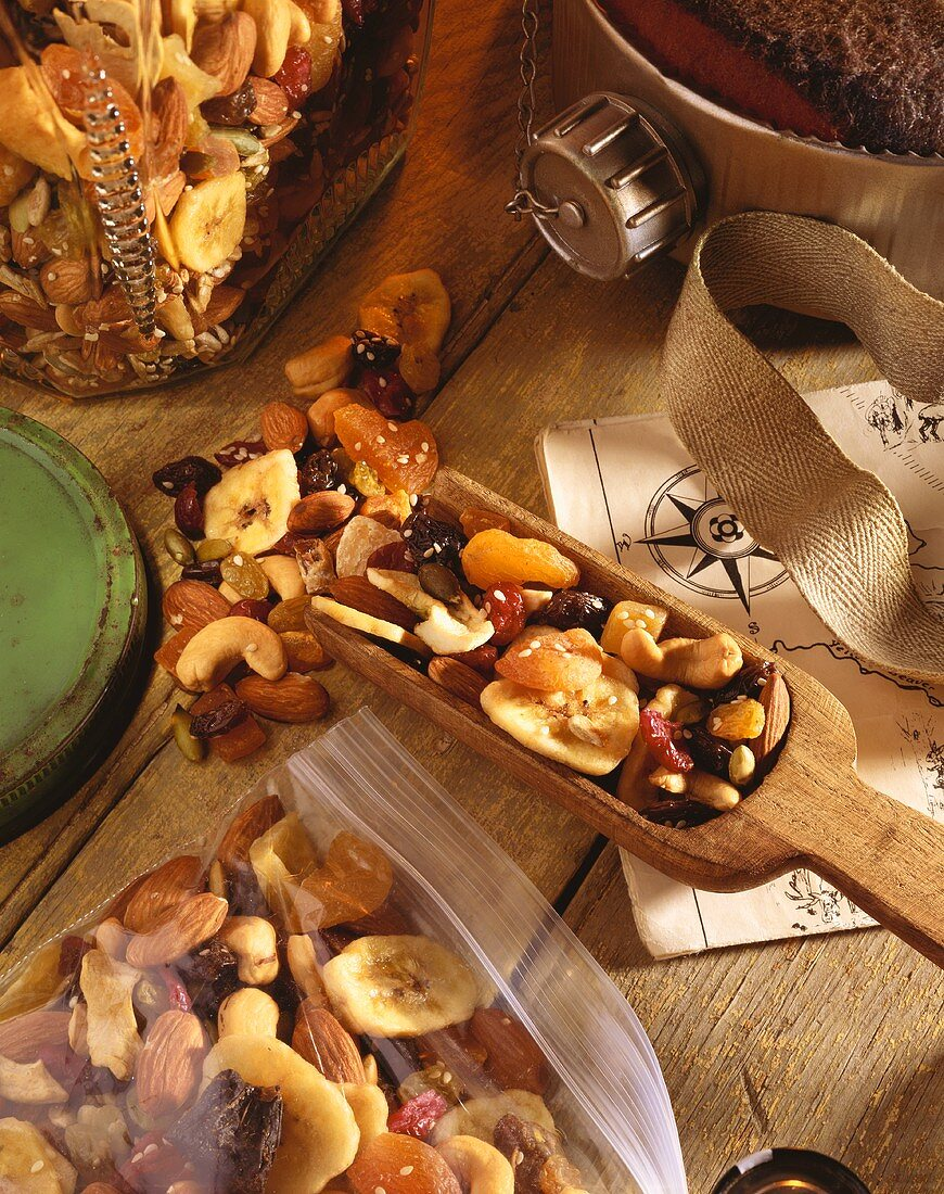 Trail Mix in a Wooden Scoop and in a Plastic Bag on Wooden Table with Map and Canteen