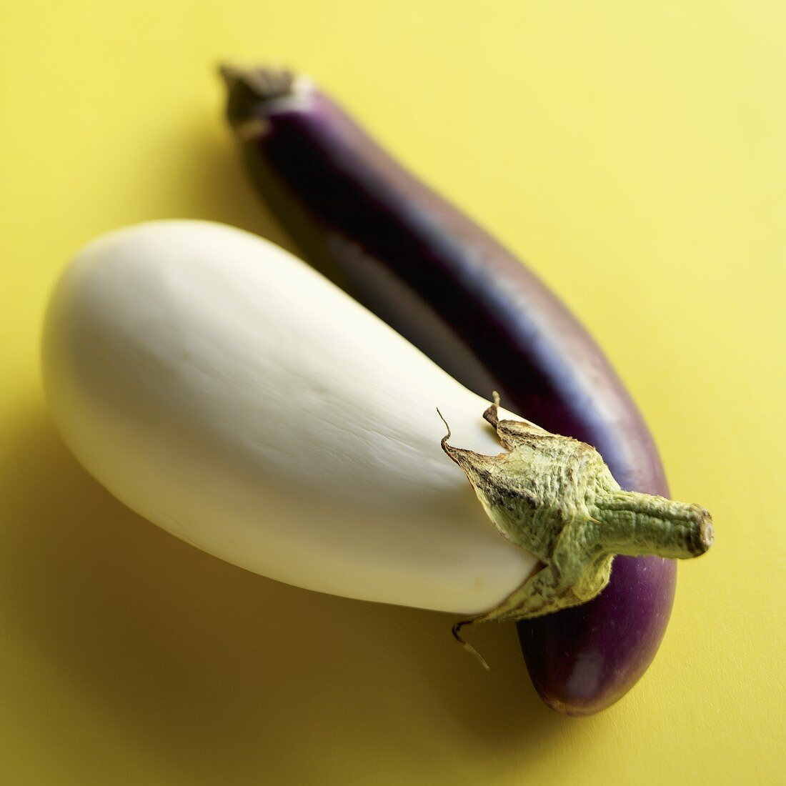 Two Eggplants, One White and One Purple