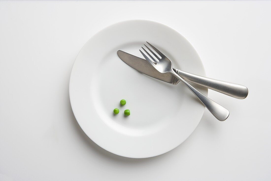 White Plate with Three Green Peas and a Knife and Fork