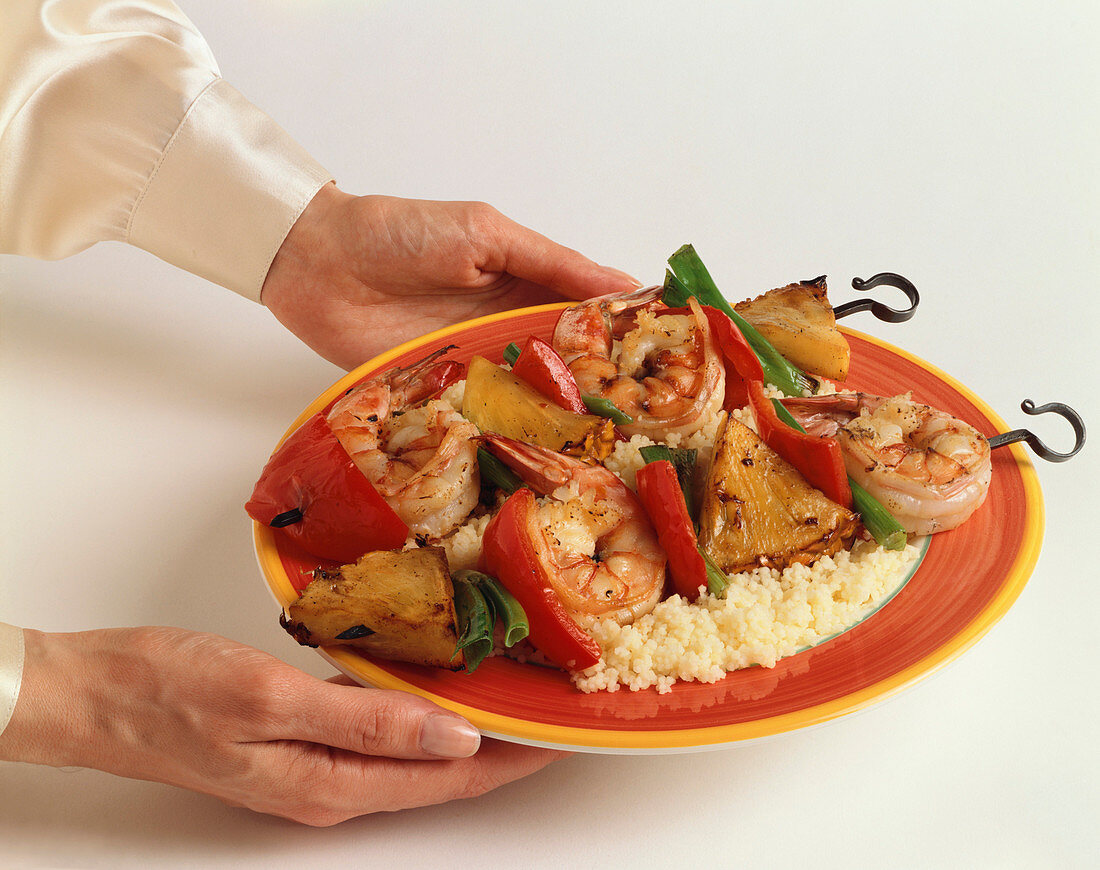 Hands Holding a Plate of Shrimp and Pineapple Kabobs Over Rice; White Background